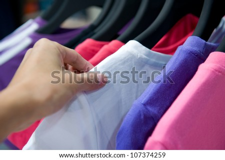Close-up of a female customer looking for T-shirts in a fashion store - stock photo
