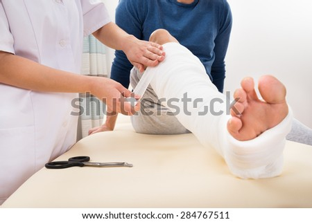 Close-up Of A Female Doctor Bandaging Patient's Leg - stock photo