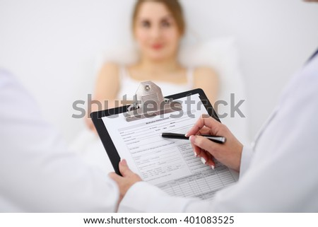 Close-up of a female doctor holding application form while consulting patient - stock photo