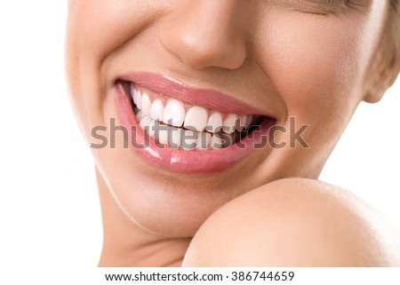 Close up of a female face with a clean white teeth smiling and being expressive wearing soft pink lipstick gloss - stock photo