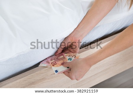 Close-up Of A Female Hand Hiding Banknotes Under Bed - stock photo