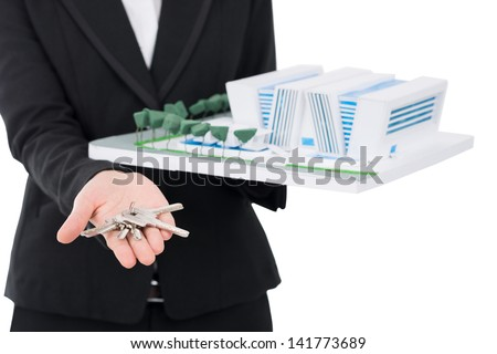 Close-up of a female hand holding a house model and keys - stock photo