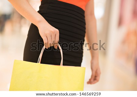 Close-up of a female hand holding a shopping bag  - stock photo