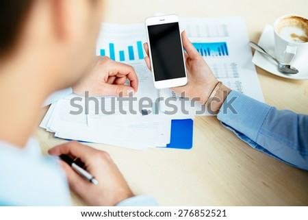 Close-up of a female hand holding a white smartphone - stock photo