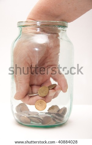 Close up of a female hand picking a money from glass jar - stock photo
