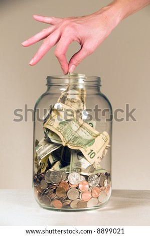 Close up of a female hand picking a twenty dollar bill out of a clear glass savings or tips bottle.