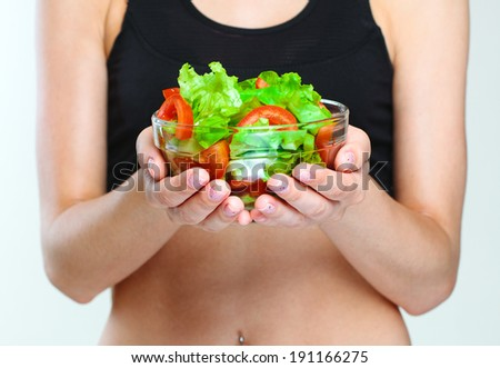 close-up of a female hands holding vegetables salad.