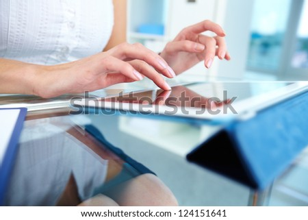 Close-up of a female touching the screen of a tablet computer - stock photo