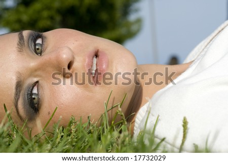 Close-up of a female wearing a white top laying in the grass on a sunny day - stock photo