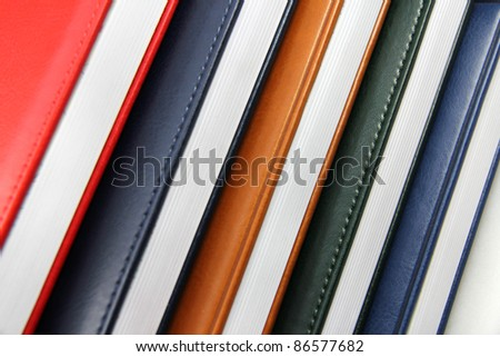 Close-up of a few colored books (notebooks, diaries). Shows a lateral, visible sheets.
