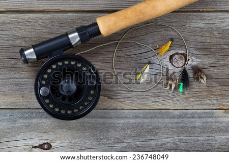 Close up of a fly reel, with line and assorted flies, and partial cork handled pole on rustic wooden boards  - stock photo