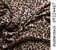 Close-up of a folds of stylish leopard scarf (cashmere background with a predatory pattern). - stock photo