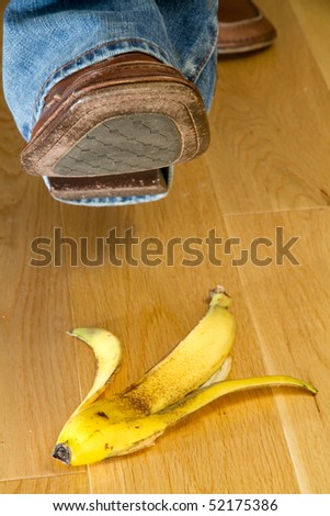 Close up of a foot about to tread on a banana skin - stock photo
