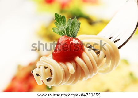 Close-up of a fork with spaghetti over pasta dishes. - stock photo