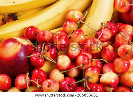 Close up of a fresh pile of fruit consisting of cherries, peaches and bananas. Layout in filled frame format.