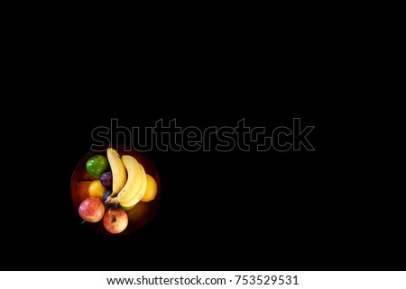Close up of a fruit bowl filled with fresh ripe fruit in an orange bowl on a black table