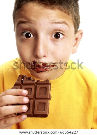 Close Up of a funny young boy eating a chocolate bar. - stock photo