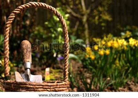 Close-up of a gardening basket containing a trowel - stock photo