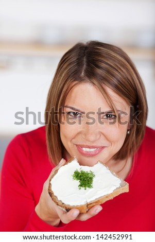 Close-up of a girl biting into a slice of bread with butter - stock photo
