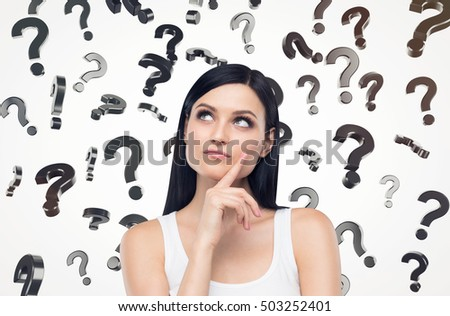 Close up of a girl in white tank top is standing against white background with blurred question marks falling from the sky. Concept of solution finding