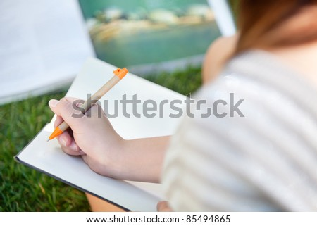 Close-up of a girl writing in a notebook - stock photo