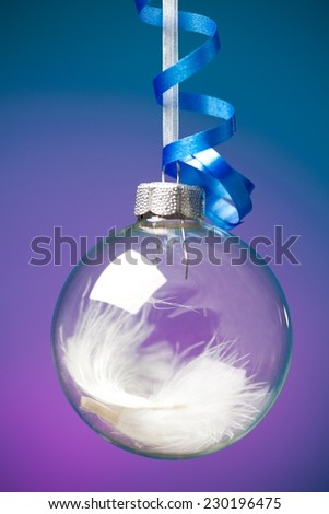 Close up of a glass Christmas decoration ball against purple background. - stock photo