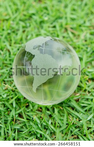 Close up of a Glass Globe on a Green Grass for Save the Green World Concept - stock photo