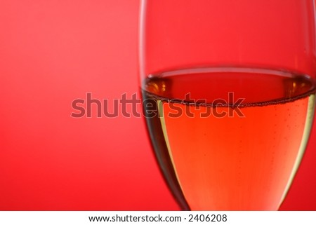 Close-up of a glass of champagne on a red background.