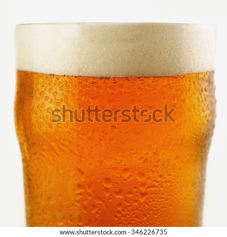 Close up of a glass of freshly pulled chilled lager beer. - stock photo