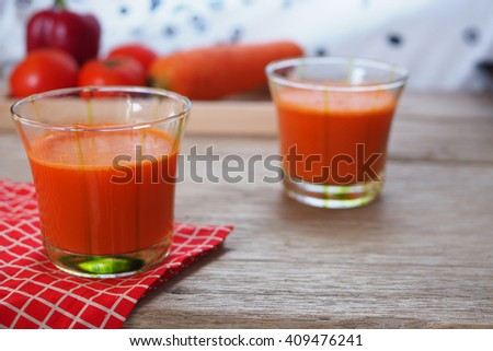 Close up of a glass of healthy mixed carrot, tomato and capsicum juice on a wooden table, selective focus.