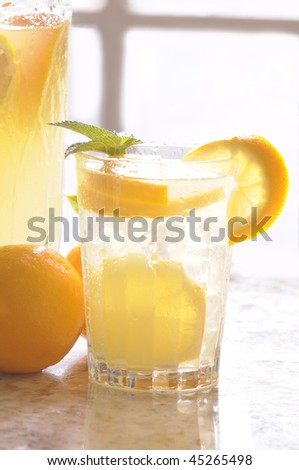 Close up of a Glass of Lemonade on counter in front of window with pitcher and lemons vertical format shallow DOF - stock photo