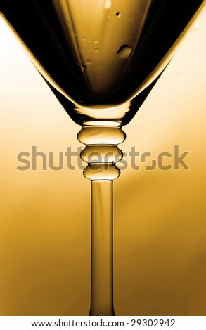Close-up of a glass of martini in drops under special illumination - stock photo