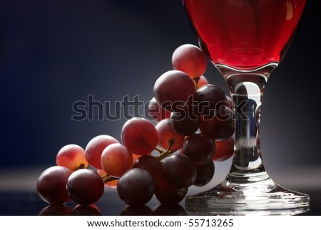 Close-up of a glass of red wine with grapes on a table - stock photo