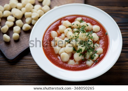 Close-up of a glass plate with potato gnocchi in tomato sauce - stock photo