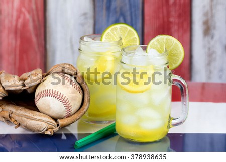 Close up of a glasses filled with cold lemonade with baseball glove and ball.  Faded wooden boards painted red, white and blue in background. Selective focus on upper front jar glass with lime slice.  - stock photo