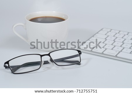 Close up of a glasses of business man business white keyboard and a coffee cup in white background