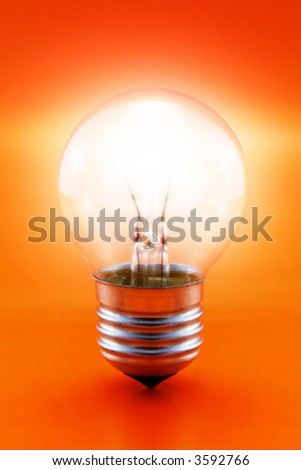 close-up of a glowing light bulb on a red background - stock photo