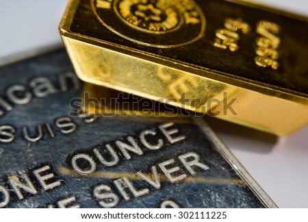 Close-up of a gold-ingot and a troy ounce silver - stock photo