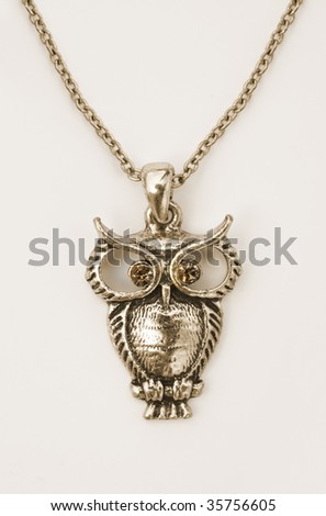 Close up of a gold owl pendant on white - stock photo