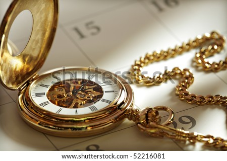 Close up of a gold pocket watch on a calendar in sunlight - stock photo