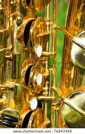 close-up of a golden brass saxophone with sun light effects