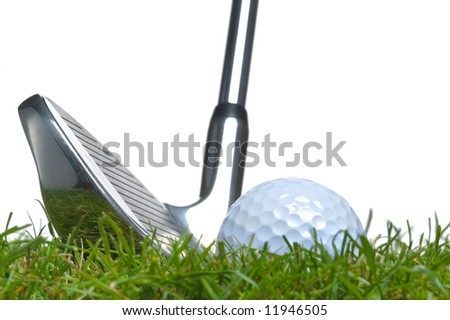 Close up of a golf ball lying in the grass with an iron club lined up for a shot. Studio shot, real grass. - stock photo