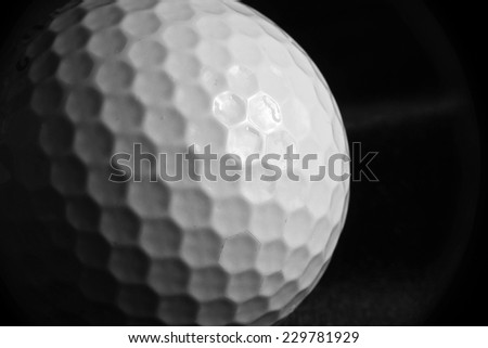 Close-up of a Golf ball on a black velvet surface with shadow cast - stock photo