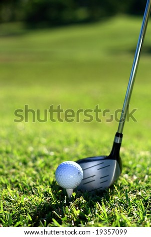 close up of a golf club, ball and tee on green grass - stock photo