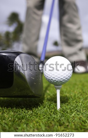 Close up of a golfer's driver with a blue shaft, ball and tee setup. - stock photo