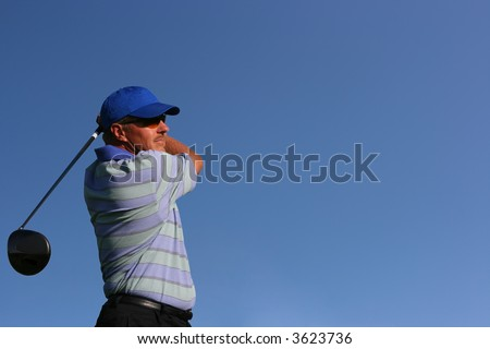 Close up of a golfer wearing a blue shirt and blue hat after teeing off on isolated blue background with copy space