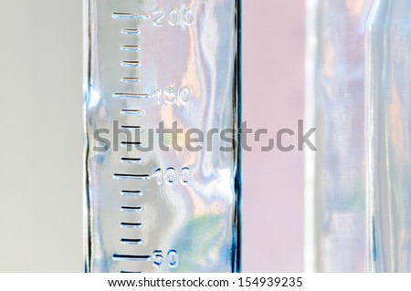 Close-up of a graduated glass bottle with colorful reflections - stock photo