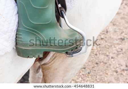 Close-up of a green booted foot in a horse's stirrup - stock photo
