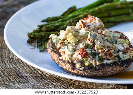 close up of a grilled stuffed mushroom served with charred asparagus and a fennel and radish salad - stock photo