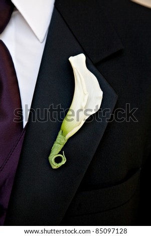 Close-up of a groom with a flower on his lapel and a purple tie